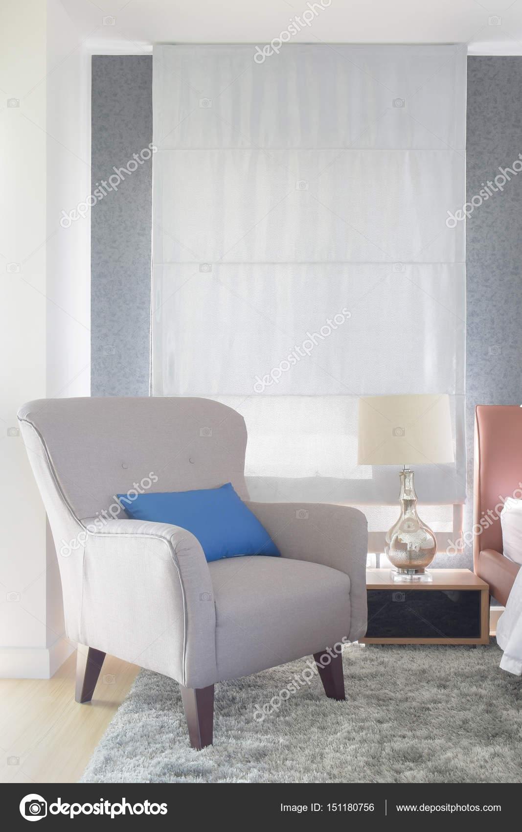 grijze bekleding fauteuil met blauw kussen in moderne interieur woonkamer stockfoto