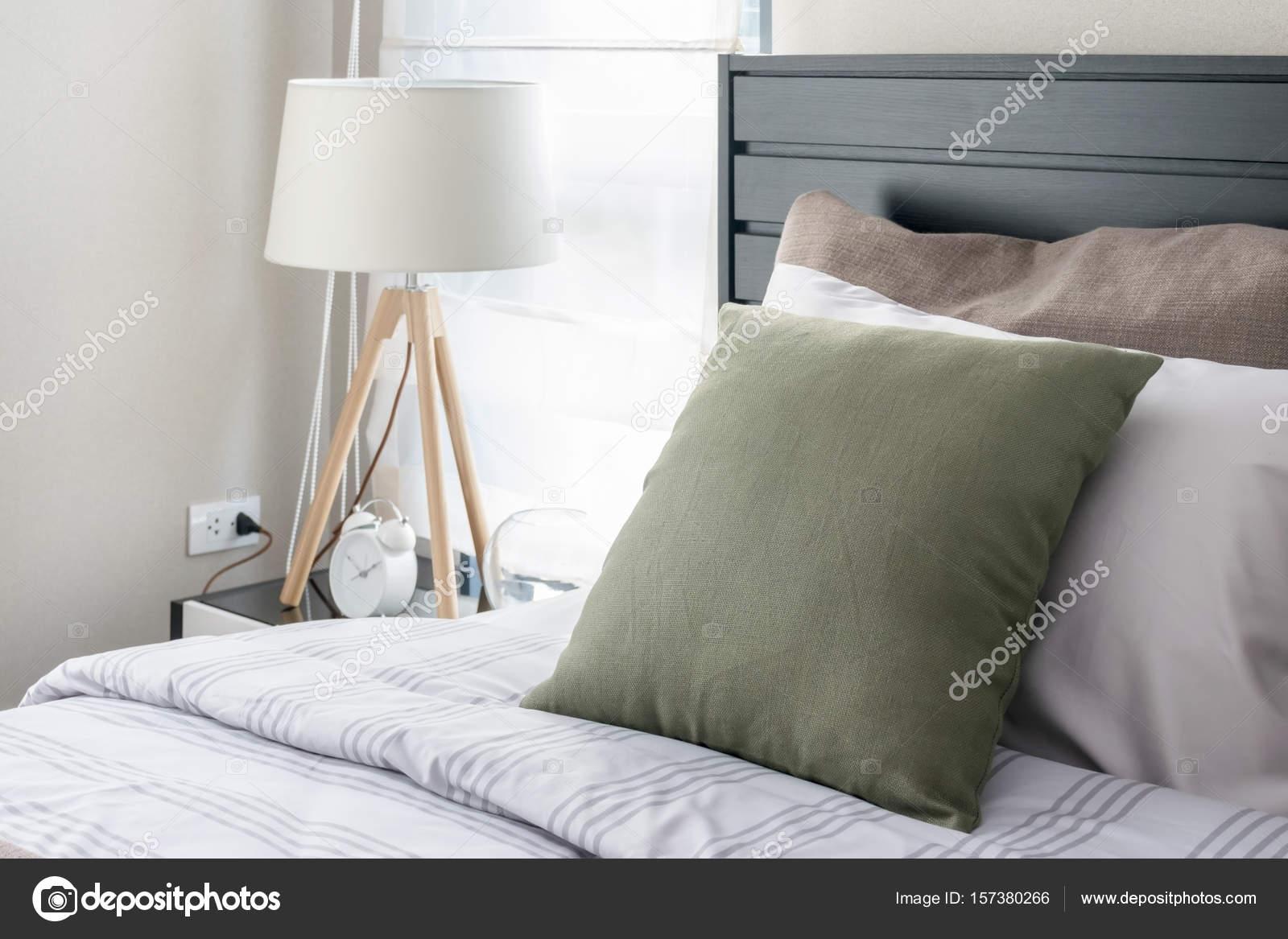 Camera da letto moderna con cuscino verde e lampada in legno
