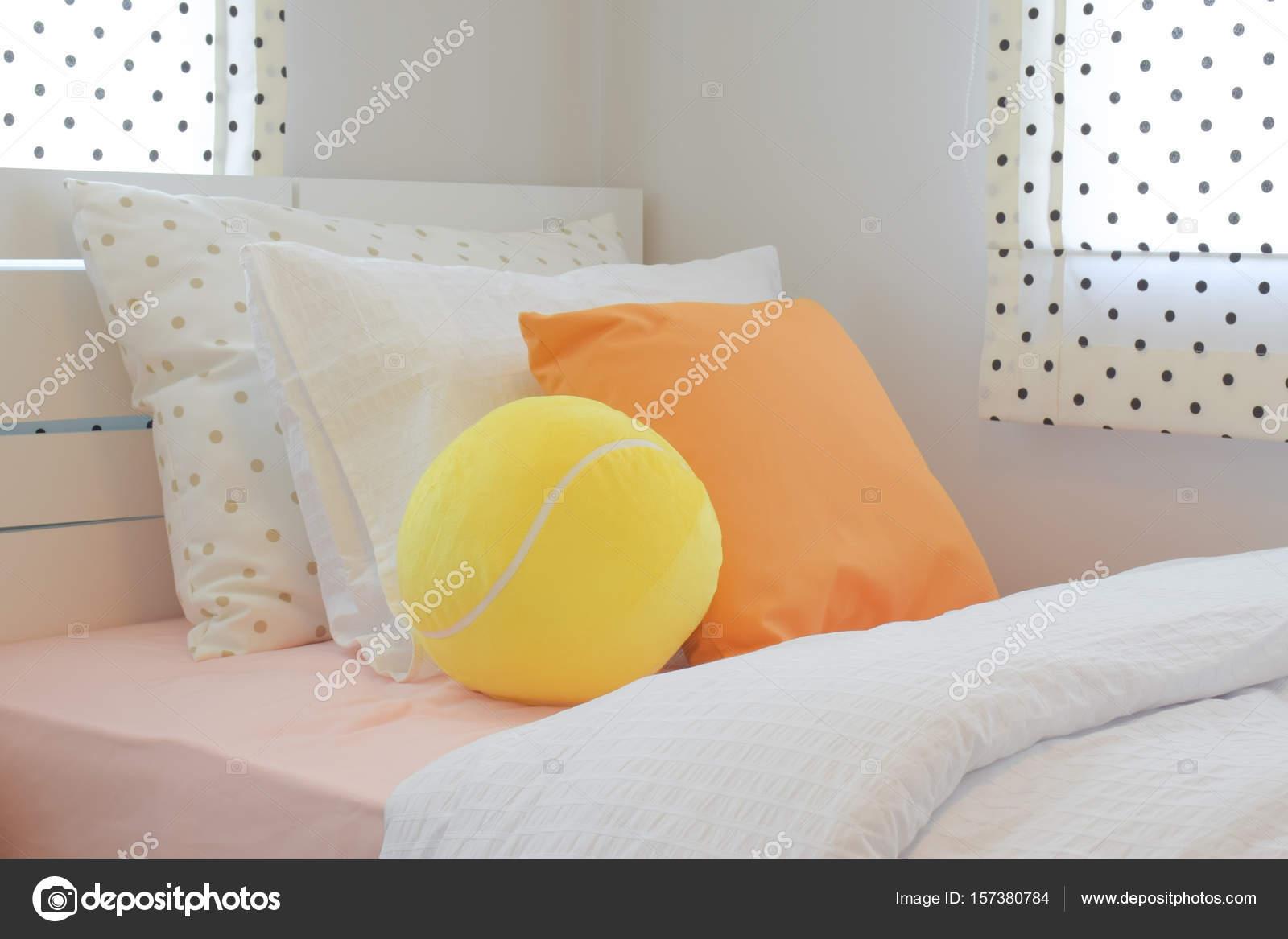 Ballon gonflé jaune et oreiller de couleur orange sur lit dans la ...