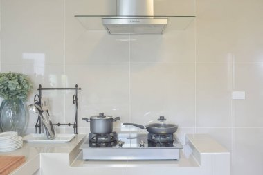 stainless pan on gas stove with utensil in modern kitchen