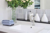 Photo washbasin with faucet and liquid soap bottle at home