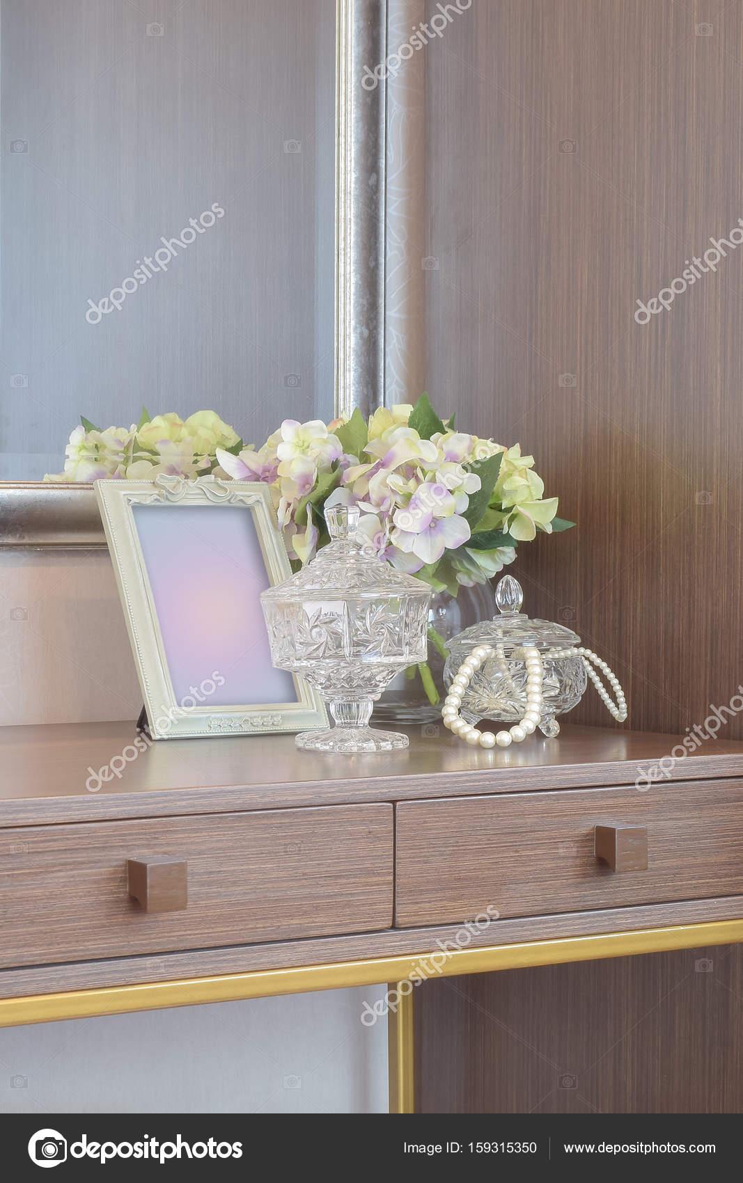 Schmuck-Kristall-Glas mit Bilderrahmen und Blumen auf dem hölzernen ...