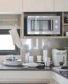 Keramické nádobí a náčiní nastavení vedle dřez v moderní kuchyni