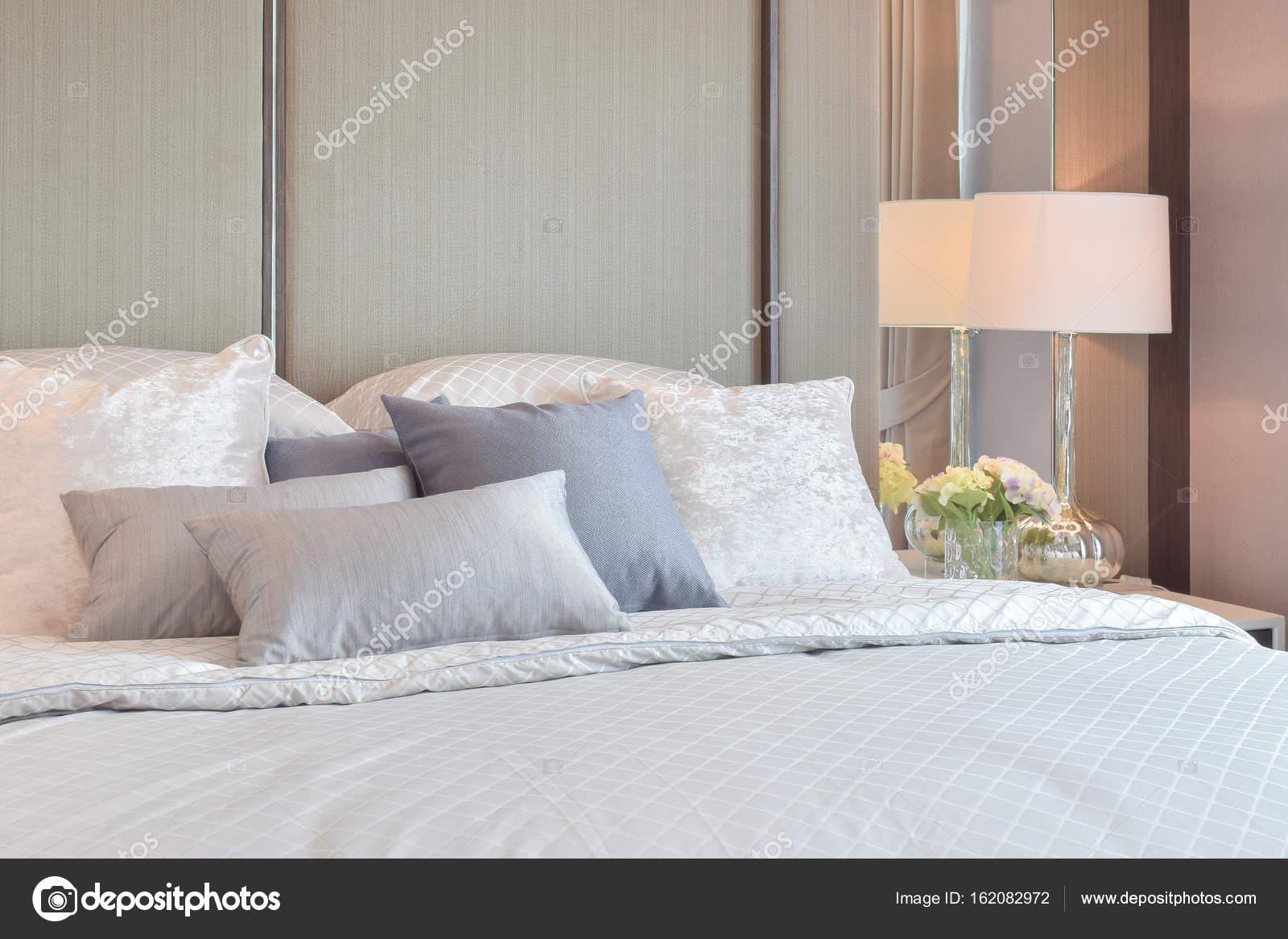 Interiore della camera da letto classica con cuscini e lampada da ...
