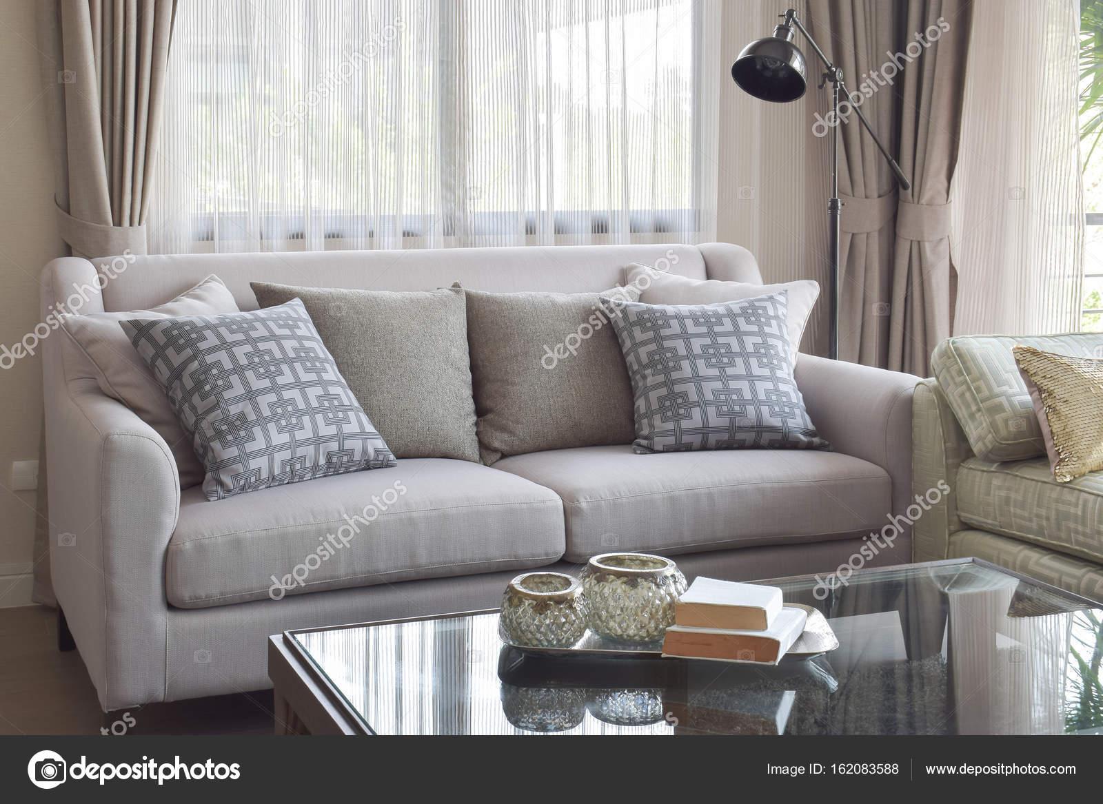 Boeken over glazen top tafel en grijze Toon sofa instellen in ...