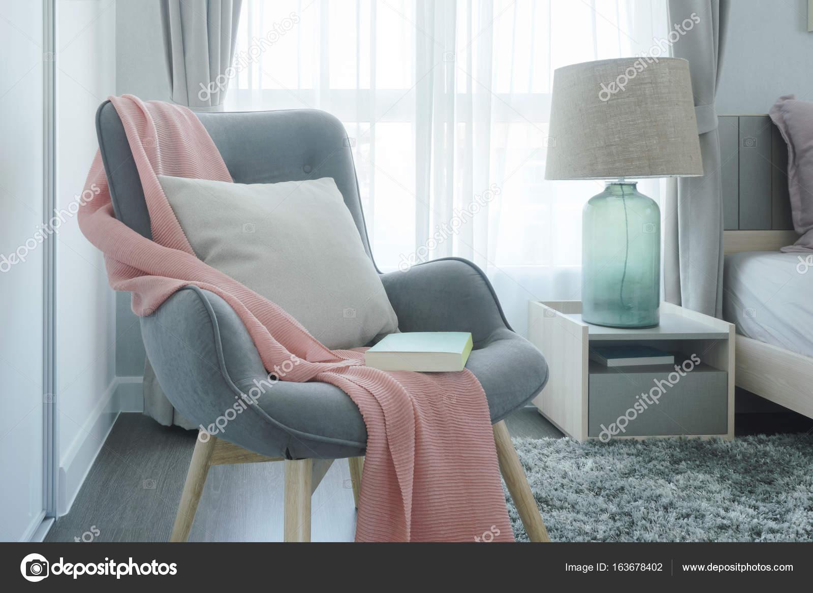 Graue easy Sessel mit rosa Schal, Kissen und Buch neben Bett im ...