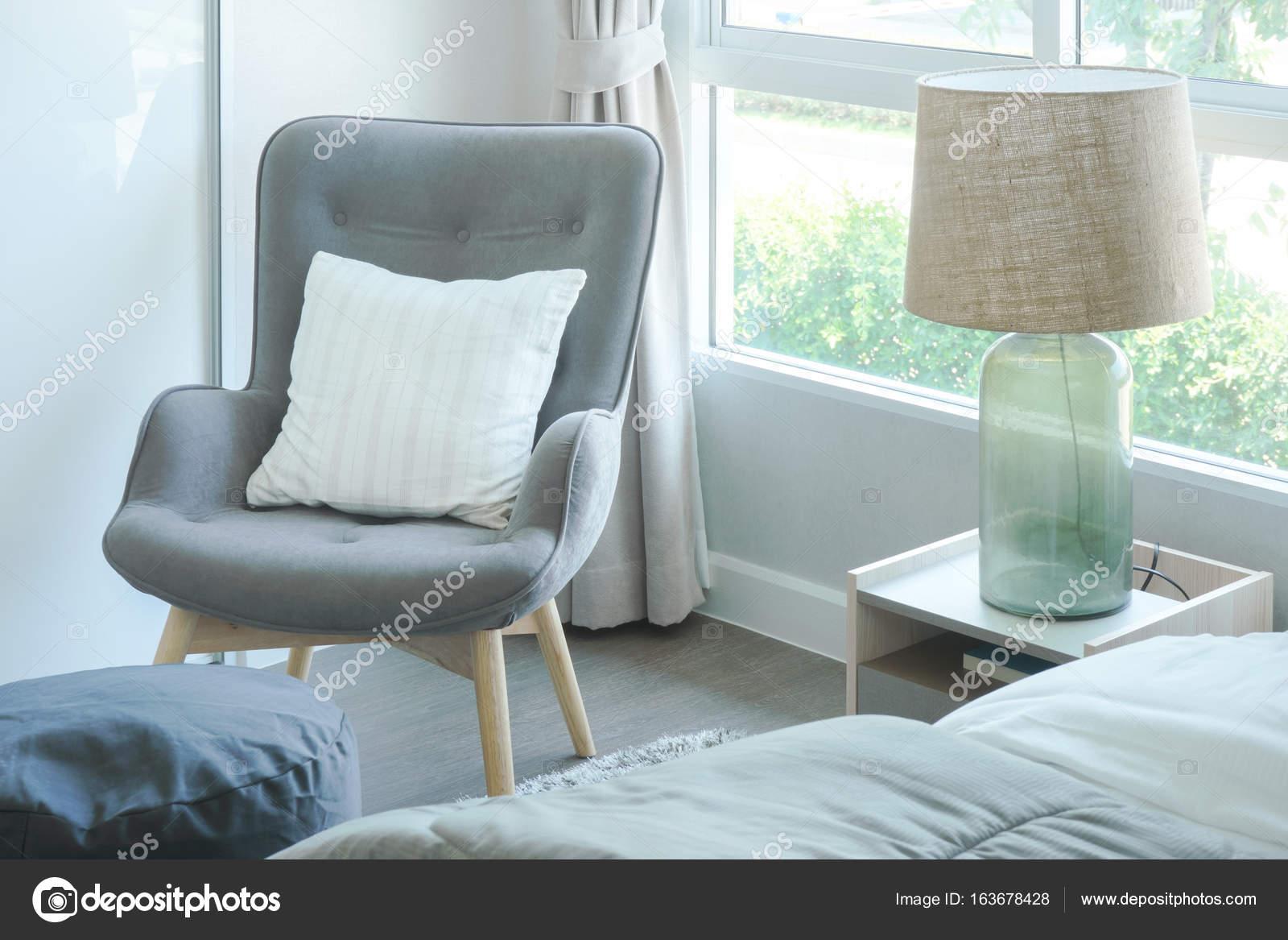 Fauteuil gris avec oreiller au coin de la chambre à coucher ...