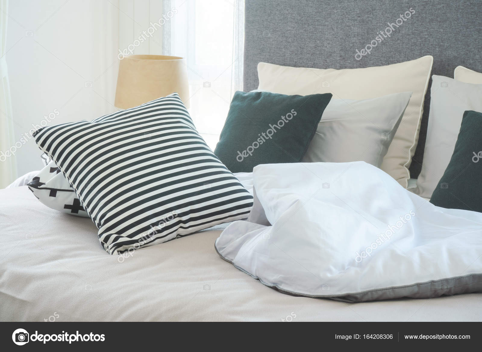 Disordinato letto con cuscini in camera da letto moderna interno