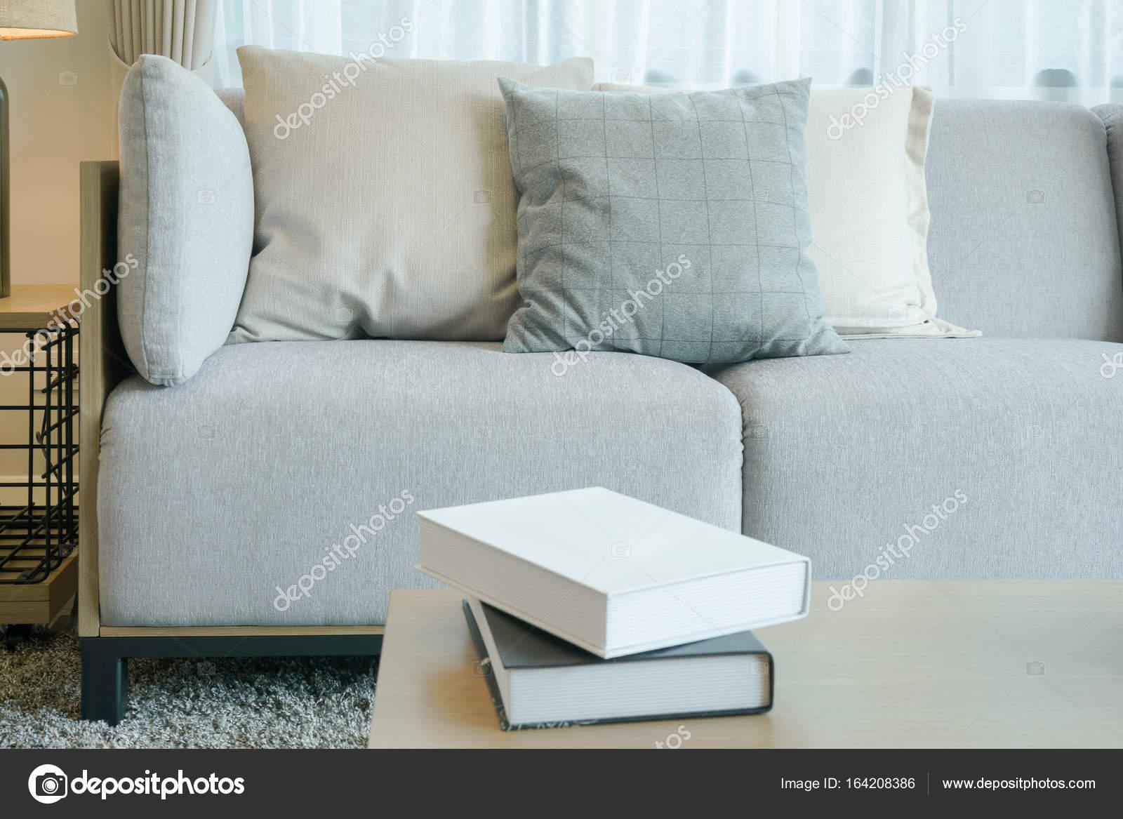 Divano grigio chiaro con cuscini in stile moderno salotto con libri ...