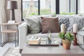 Barna és textúra párnák bézs kanapé a gyertyák, a fából készült asztal
