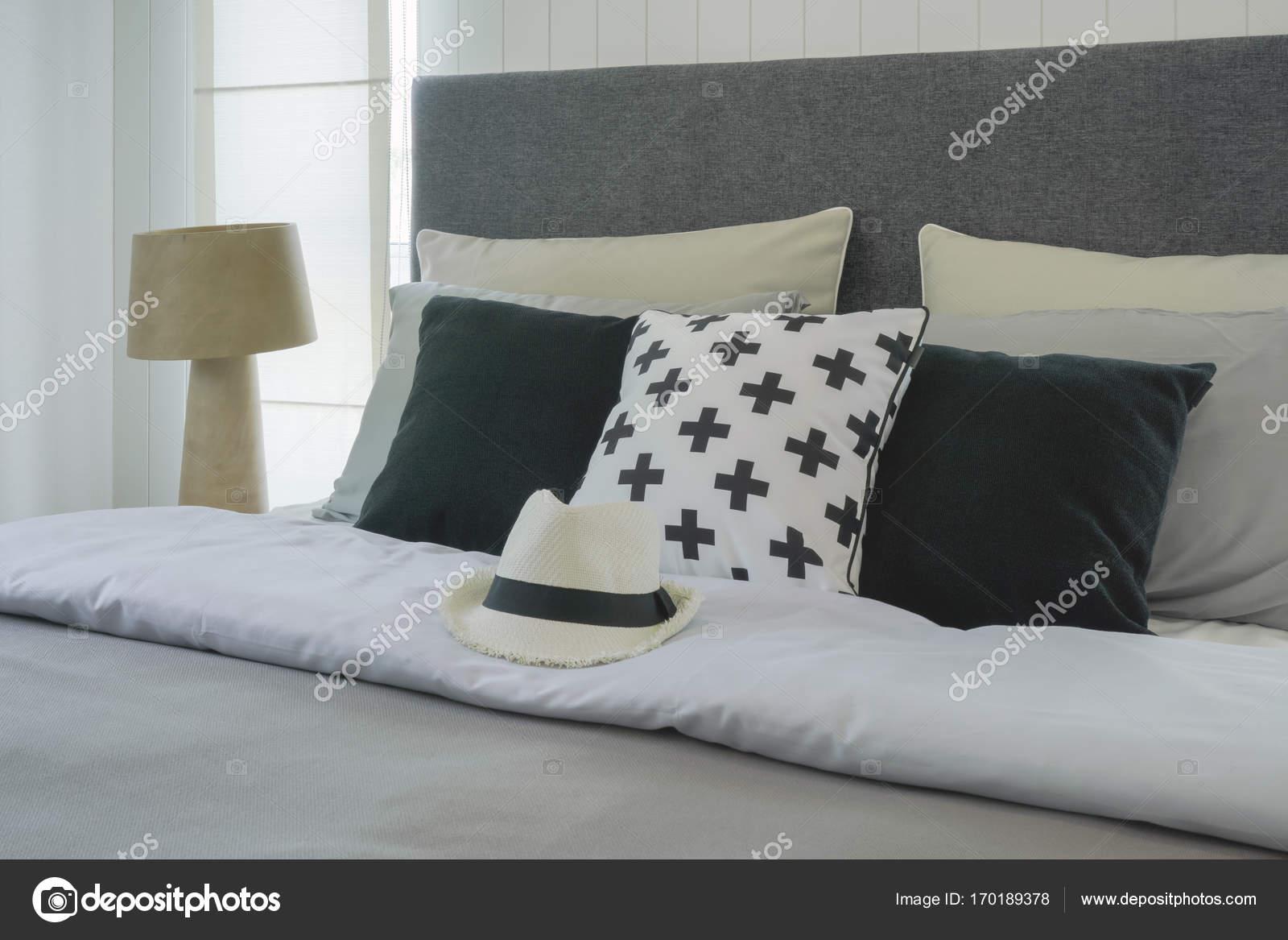 Cappello sul letto con cuscini in interiore elegante camera da letto ...