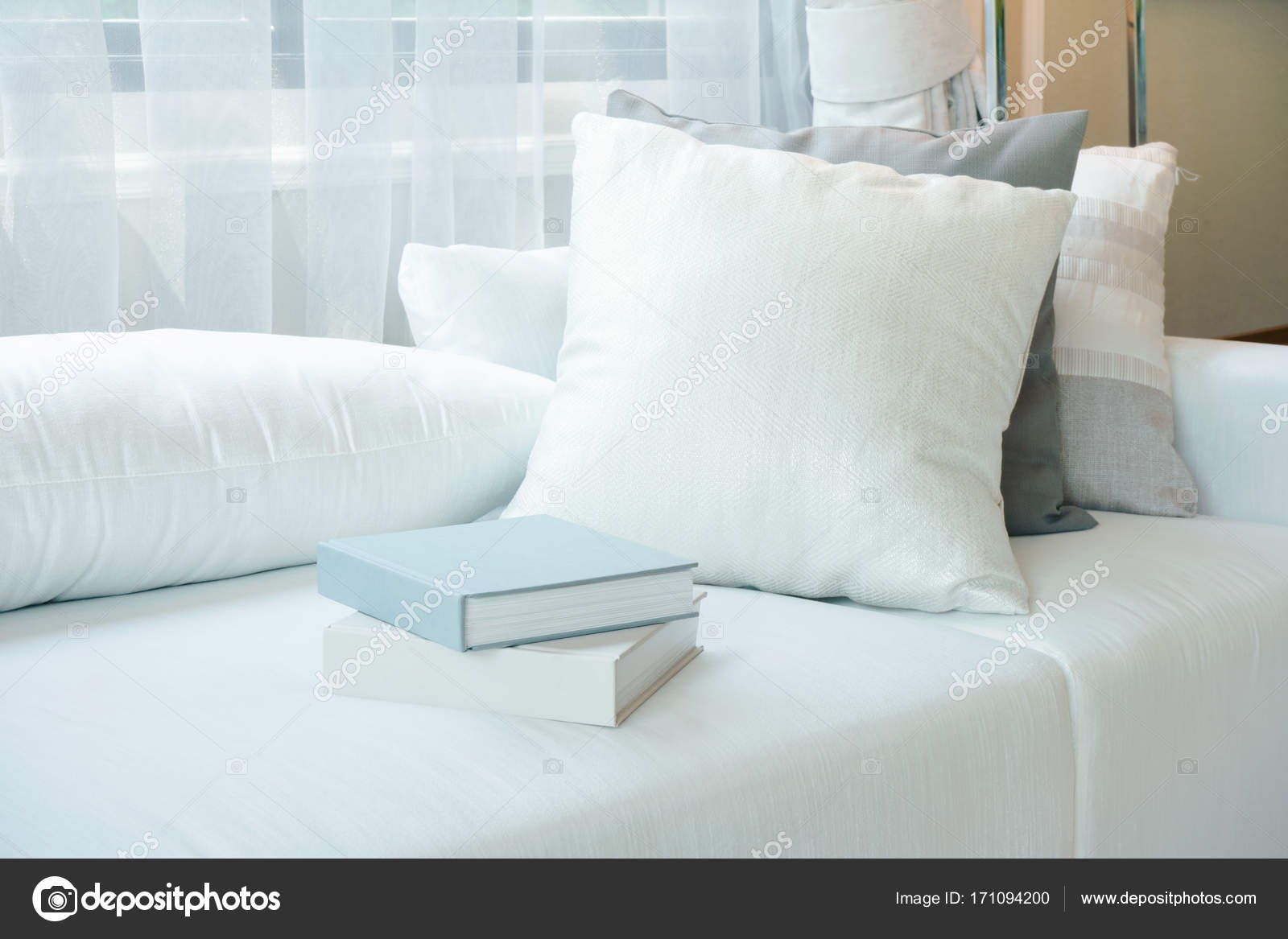 White pillows and books setting on white sofa in modern living room ...