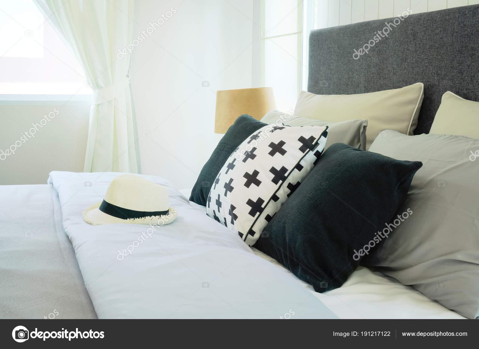 Cappello sul letto con cuscini in interiore elegante camera ...
