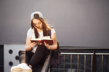 Pretty girl sit on the steps and read book with headphones