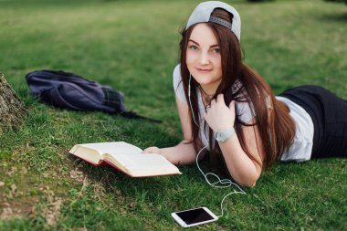 Pretty girl read book and listen music at park