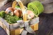Fotografie Ein Korb mit Ostereiern und einer Schleife liegt auf dem Holztisch. .