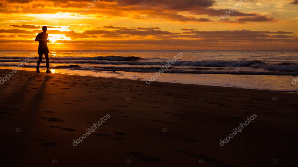 Man is running by the beach at sunrise.