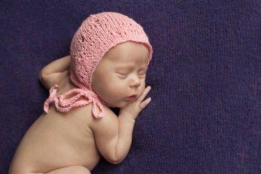 sleeping newborn baby in pink cap