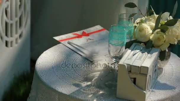 Ženská ruka užívat dvě prázdné sklenice šampaňského z tabulky s svatební certifikát během obřadu