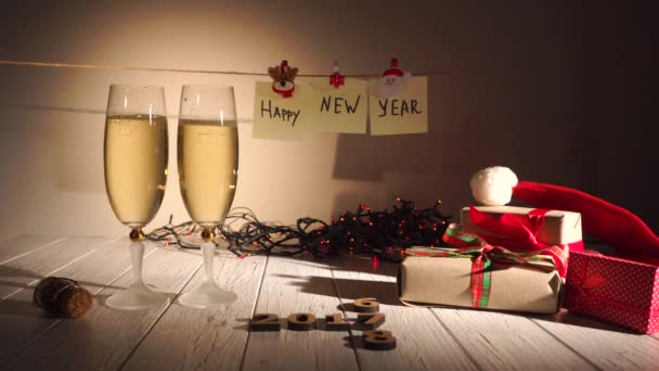 Man gießt Champagner in ein Glas, Silvester und Weihnachtsfeier mit Champagner. Zwei Flöten und gießt Sekt aus der Flasche. Feiertagsdekorationen