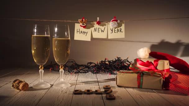 Silvestrovské a vánoční oslava šampaňským. Dvě flétny a nalévání šumivého vína z láhve. Sváteční dekorace