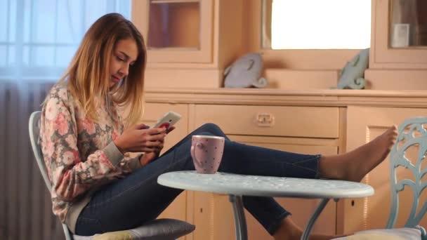 fiatal gyönyörű tizenéves lány ült az asztalnál, a nappaliban, használ smartphone, csevegni a barátaival, teázás, vicces párnák a szekrény