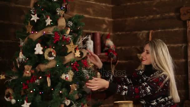 Belle jeune femme jouant avec des boules de Noël dans la jolie maison  décoration et rire