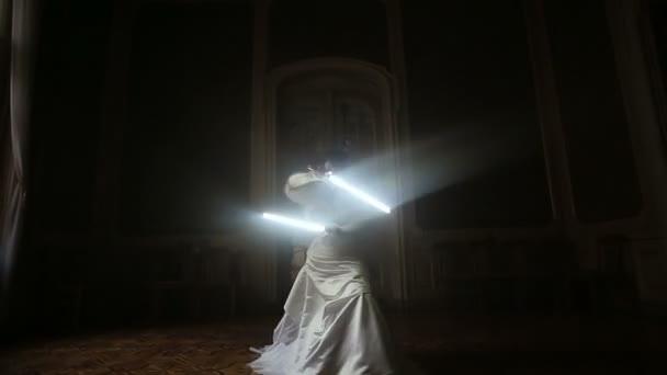 Silhouette einer hübschen fröhlichen Braut, die mit Lichtschwert spielt.