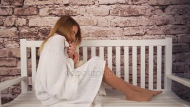 young teenage girl feeling sick. She sitting on the bench and hugging a teddy bear. Covered her body with white coverlid