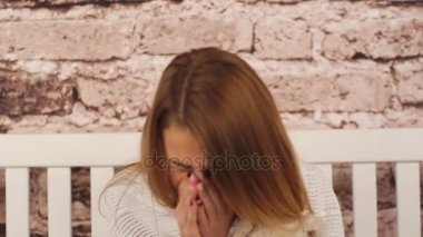 young teenage girl feeling sick. She sitting on the bench, hugging a teddy bear and sneezing. Her sore is throat. Covered her shoulders with white coverlid.