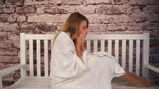 young teenage girl feeling sick. She sitting on the bench, hugging a teddy bear and sneezing. Covered her body with white coverlid
