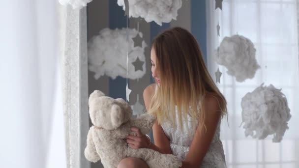 Mooie jonge meisje speelt met de teddybeer in haar slaapkamer. ze