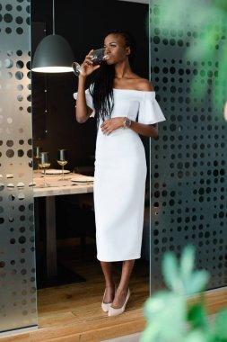 Sexy pretty african girl in restaurant with modern design. She is wearing midi white dress with bare shoulders and drinking red wine.