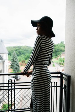 Pretty attractive woman with dark skin is standing on the balcony and looking at somewhere. Model in stripped dress and black hat.