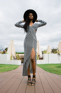 Charming, pretty, tender, beautiful african woman wearing dress in stripes and black hat on her head. Model staying on luxury hotel terrace