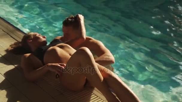 sexy Paar Schwimmen im Hotelpool. Mann sucht aufregende Mädchen. Blonde Frau auf dem Rand des Pools liegen. Sie setzen ihre Hand in die Haare mans, ihn umarmen und lächelnd