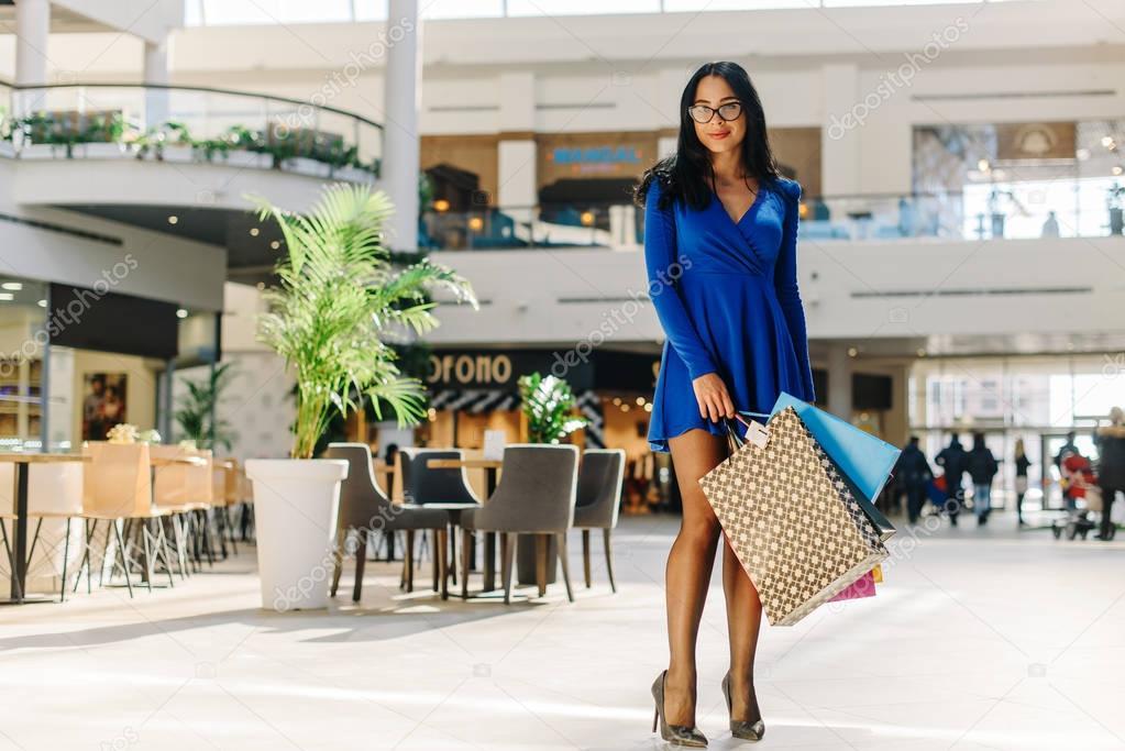 391f74359dc8 Γοήτευσε ελκυστική γυναίκα εν ολίγοις μπλε φόρεμα με μακριά μανίκια σε  μαύρο ψηλά τακούνια και τα γυαλιά μετά τις αγορές σας. Θηλυκό έχει πολλές  πολύχρωμες ...