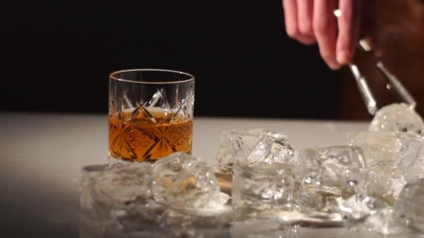 Csapos egy jég labda figyelembe véve az üveg wiskey. Inni az spleshing oldalán. Sötét és árnyékok
