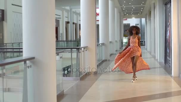 Fiatal vonzó afrikai lány séta a kereskedelmi központjában, a gyönyörű narancssárga ruháját szórás
