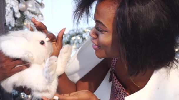 Atractiva afrikanische Frau mit niedlichen weißen Kaninchen in der Nähe von Neujahr Baum zu spielen. Urlaubszeit. Kaninchen in Geschenkbox. Haustier in mans Hände. Hübsches Mädchen mit Lächeln im Gesicht