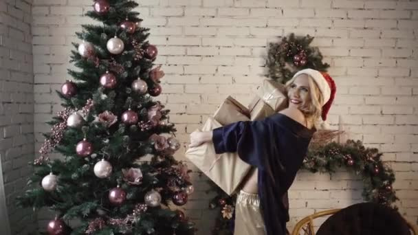 Fiatal szexi lány, szép fehérnemű boldog-hoz tart egy csomó ajándék a karácsonyfa közelében