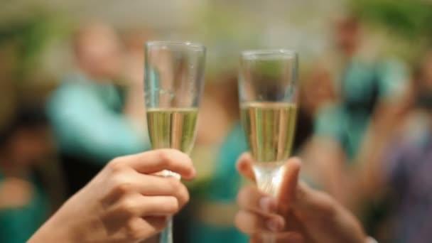 Braut und Bräutigam klimpern fröhlich mit Hochzeits-Champagnergläsern und feiern ihre Hochzeit