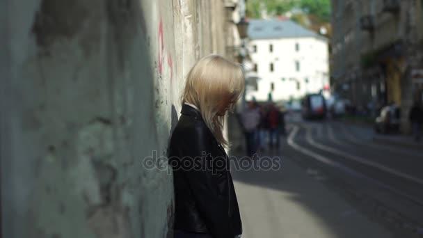 Krásná blond dívka stojící vedle staré zdi v centru města