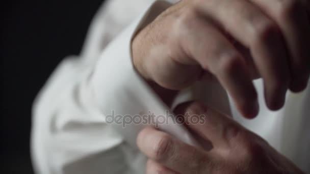 523bcaeb279d Ο άνθρωπος κουμπιά επάνω μανικετόκουμπα σε λευκό πουκάμισο– πλάνα αρχείου