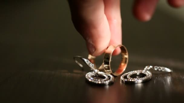 Man throws golden wedding ring on wooden table