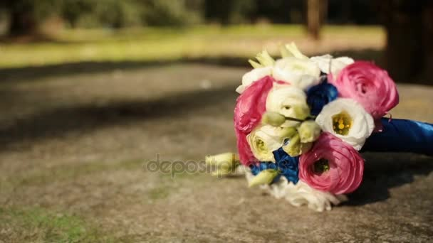 Wedding bouquet of pink, white and blue flowers lies on the path