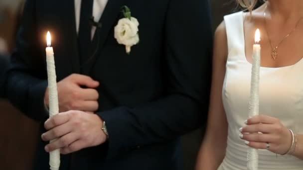 Newlyweds cross themselves holding white burning candles