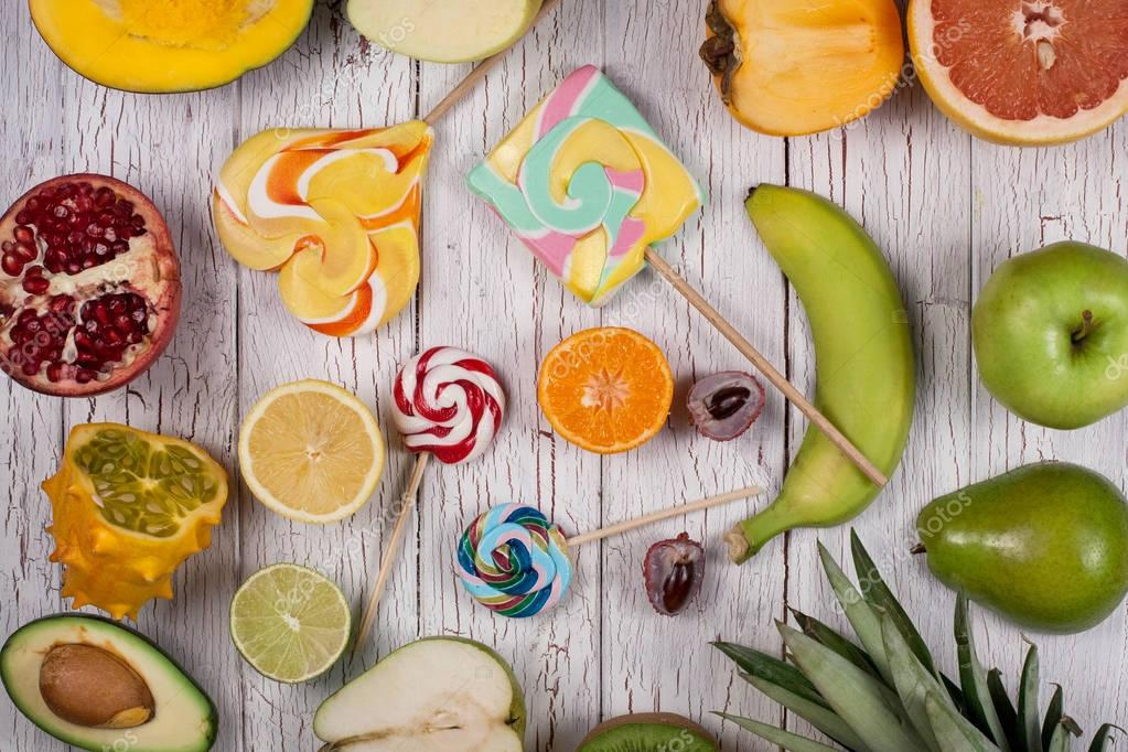 Colourful composition of candies and tropical fruits cut into halves placed on a white wooden board