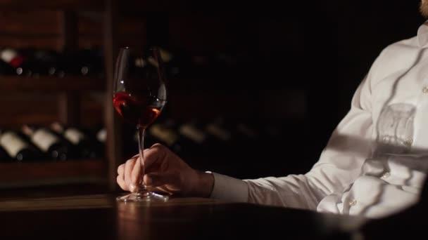 Člověk ruku drží sklenici červeného vína na dřevěný stůl v pozadí rozmazané lahví vína.