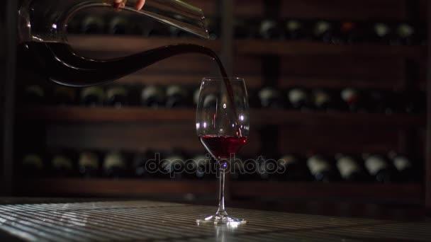 Žena je tmavě červené víno z karafy nalil do skla umístěných na dřevěný stůl v sklad vína.
